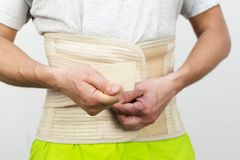 Man dressing back support belt by his hands, front view royalty free stock image
