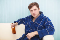 Man in dressing gown sits on a couch with bottle Royalty Free Stock Photography