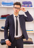 Man in dressing room. Stylish handsome man in glasses standing in dressing room and looking at camera Stock Images