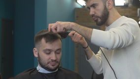 A man dries hair to men in the barbershop stock footage