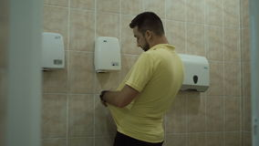 The man is drying his hands in the toilet. The man dries his hands and t-shirt in the toilet and using a hand dryer stock video