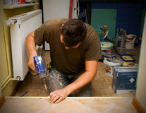 Man with drill. Man will drill renovating interior floor Stock Photo