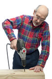 Man with drill. Retired senior citizen uses an electric drill to put a hole in wood Royalty Free Stock Photography