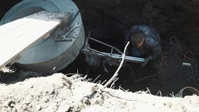 Man drill circular hole in concrete chamber manhole ring using industrial drill stock video