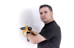 Man with a drill machine. In his hand drilling a wall Royalty Free Stock Photo