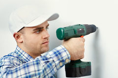 Man with drill making hole in wall Stock Photo