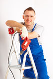 Man with drill standing on ladder. Cheerful man working with red drill, wearing protective glasses, blue trousers and gloves, standing on ladder Stock Images