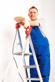 Man with drill standing on ladder Stock Images