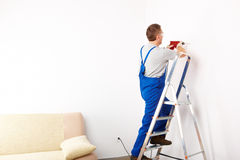Man with drill working on ladder. Man working with red drill, wearing protective glasses, blue trousers and gloves, standing on ladder Stock Photography