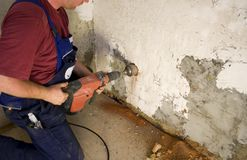 Man drilling. Hole in wall Stock Photos