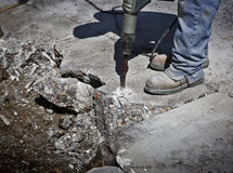 Man drilling cement concrete road Stock Images