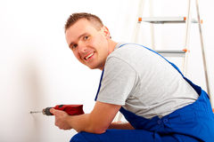 Man drilling hole. Cheerful man working drilling hole in white wall in home, ladder in background Stock Image