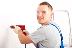 Man drilling hole. Cheerful man working drilling hole in white wall in home, wearing protective clothes trousers, gloves and glasses, ladder in background Royalty Free Stock Photography