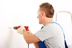 Man drilling hole. Man working drilling hole in white wall in home, wearing protective clothes trousers, gloves and glasses, ladder in background Stock Photography