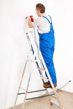 Man drilling hole standing on ladder Stock Photo