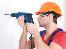 A man drilling a hole in the wall. Royalty Free Stock Image