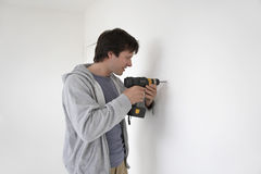 Man Drilling Hole In Wall royalty free stock photography