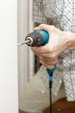 Man drilling a hole in a wooden door Stock Image
