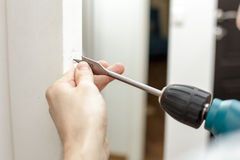 Man drilling a hole in a wooden door Stock Photo