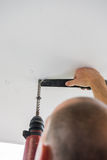 Man is drilling holes into concrete ceiling with drilling machin Royalty Free Stock Photography