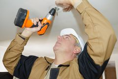 Man drilling holes into concrete ceiling with drilling machine. Man is drilling holes into concrete ceiling with drilling machine Stock Image