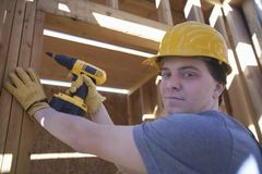 Free Man Drilling On A Wooden Beam At Site Royalty Free Stock Photos - 29666808