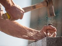 Man drilling rock with chisel and sledge hammer stock photo