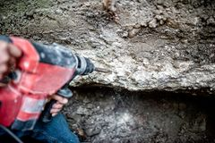 Man with drilling tool and professional machinery. Destroying a concrete wall underground Royalty Free Stock Image