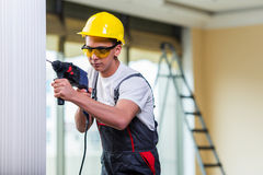 The man drilling the wall with drill perforator Stock Images