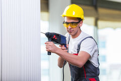 The man drilling the wall with drill perforator Stock Image