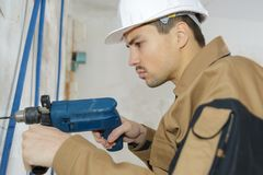 Man drilling wall with drill perforator Stock Images