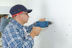 Man drilling wall with impact drill. Man drilling the wall with impact drill stock photography