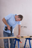 Man drilling wood on sawhorse Stock Image