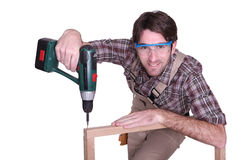 Man drilling into wooden frame Royalty Free Stock Photography