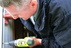 A man drills with a drill, accumulator.. Power of electric screwdriver. Close up.  stock photography