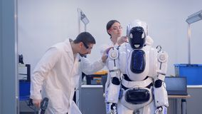 Workers fix a robot. stock footage