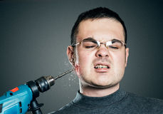 Man drills till it bleeds the cheek. Toothache, pain and masochism concept. Studio shot. Grainy gray background. Man drills till it bleeds the cheek. Toothache Royalty Free Stock Photography
