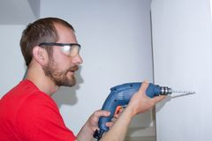 A man drills a wall with a drill. Worker at home royalty free stock images