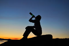 Man drink alcohol on the shore Stock Images