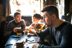 Man drink beer in front of to discussing drinking friends in pub. Friends in pub. Royalty Free Stock Photography