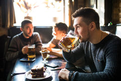 Man drink beer in front of to discussing drinking friends in pub. Friends in pub. Stock Photography