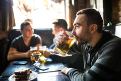 Man drink beer in front of to discussing drinking friends in pub. Friends in pub. Royalty Free Stock Image