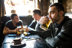 Man drink beer in front of to discussing drinking friends in pub. Friends in pub. Man drink beer in front of to discussing drinking friends in pub Stock Photography