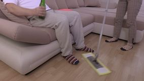 Man drink beer and using remote control.Woman using mop. In room stock video