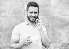 Man drink cappuccino speak phone grey wall background. Reasons entrepreneurs drink coffee. Even if you drink coffee on stock photo