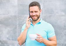 Man drink cappuccino speak phone grey wall background. Reasons entrepreneurs drink coffee. Even if you drink coffee on stock images