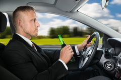 Man drink's beer while driving car Stock Photo