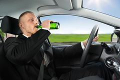 Man drink's beer while driving car Royalty Free Stock Images