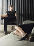 Man With Drink And Woman Lying On Sofa Royalty Free Stock Photo