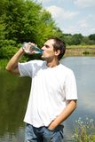 Man  drinking. Young man eagerly drinking water from a bottle Stock Image